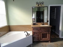 Bathroom Remodeling New White Tub and Dark Brown Vanity with Dark Granite Countertops and Backsplash.