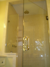 Bathroom Remodeling New Walk-In Shower with Beige Tiles. Bronze Colored Ceiling Mounted Showerhead. and Hardware. Glass Door with Brass Handle