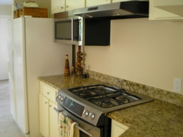 Kitchen Remodeling New Stainless Steel Gas Range with Hood Vent, Microwave and Granite Countertops